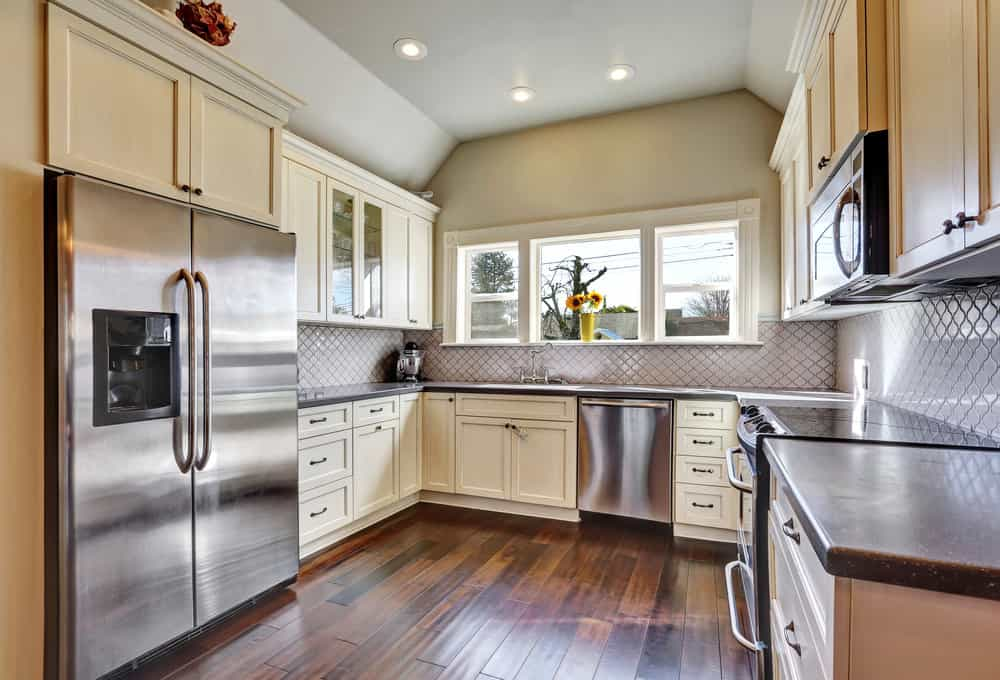The gray cove ceiling of this small and charming kitchen is complemented by the dark countertop of the U-shaped peninsula. There is no space for a kitchen island in this room but it makes up with a beautiful hardwood flooring to contrast the shaker cabinets and drawers.