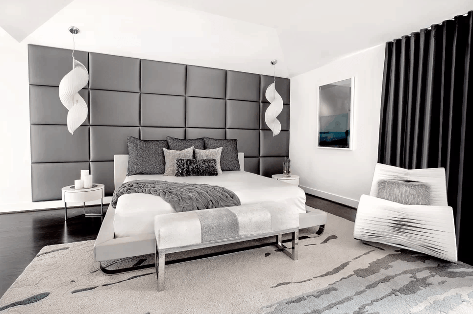 This is a bright primary bedroom that is balanced by the shades of gray against the white elements such as the white bed, white walls and the brilliant white cove ceiling that hangs a couple of decorative spiral lights on either side of the large gray cushioned headboard.
