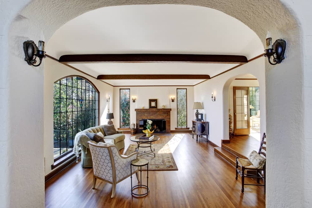 The white and bright living room has a large and tall arched window behind the curved cushioned sectional sofa. This complements the hardwood flooring that contrasts the white walls and the white cove ceiling that has a couple of exposed dark wooden beams.