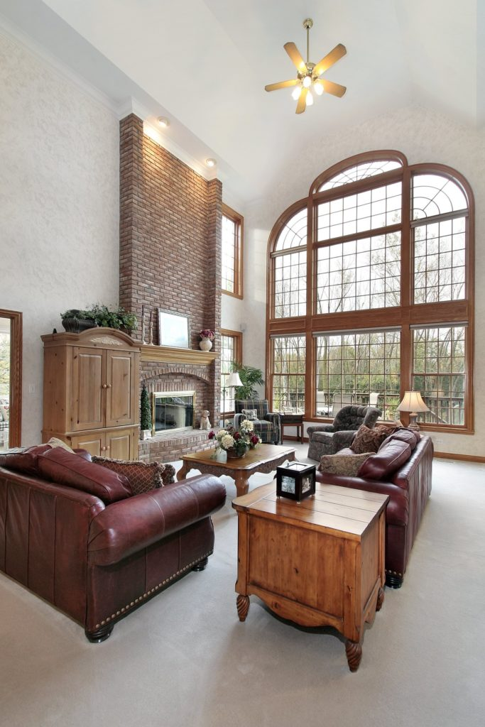 The tall ceiling of this living room has a curvature that is followed by the tall arched window. Adjacent to this is the tall red bricked panel of the fireplace that is paired with a couple of red leather cushioned sofas with a wooden coffee table that matches with the wooden cabinet beside the fireplace.
