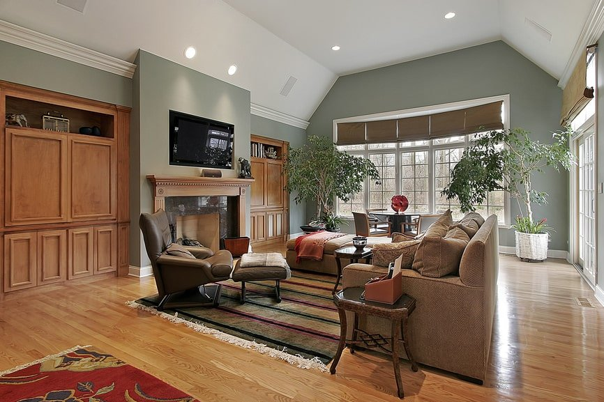 The white cove ceiling of this spacious living room has recessed lights that augment the natural lights coming in from the tall row of windows by the informal dining area on the far side. The living room has a fireplace with a wooden mantle that stands out against the light green walls.