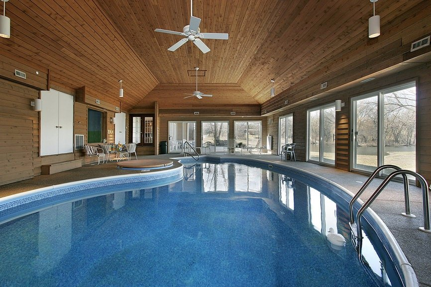 This is a large indoor curved pool brightened by the row of sliding glass doors that bring in an abundance of natural lighting. This is topped with a large cove wooden ceiling with a plank shiplap finish that brings a certain spa charm to this indoor pool area.