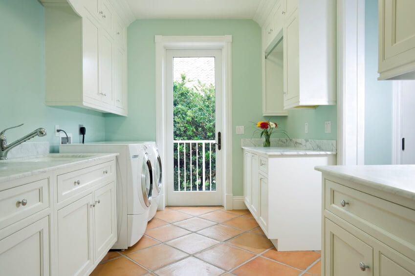 This is a charming and simple laundry room with a white cove ceiling connecting to the hanging cabinetry that stands out against the light green walls. This is also given terracotta flooring tiles to give an earthy contrast to the bright white appliances and cabinets.