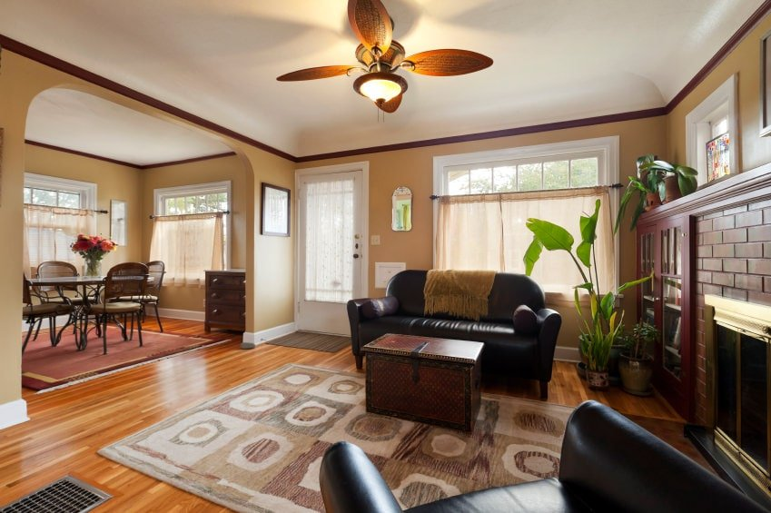 The ceiling fan stands out against the white cove ceiling with its brown decorative blades and the yellow dome light attached to it. This matches well with the brown walls blending with the brown cabinetry beside the fireplace that has brown bricks on its mantle.