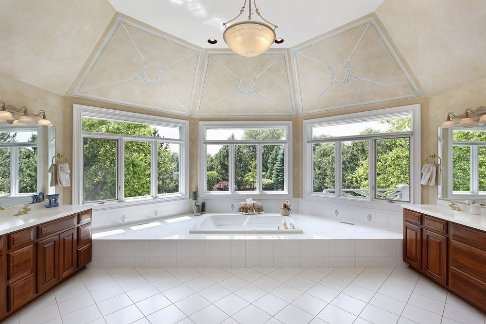 This large primary bathroom has a white porcelain bathtub placed at the far end in the middle of the row of tall windows. These are then connected to the cove ceiling that has the same beige tone as the walls complemented by the dark brown vanities.
