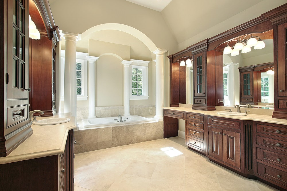 The beige cove ceiling of this bathroom blends well with the beige walls and the beige alcove of the bathtub that has white pillars and white windows matching the white porcelain bathtub. These are then contrasted by the large wooden structures of the vanities.