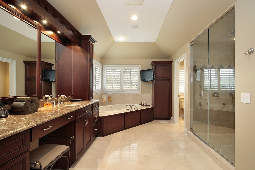 The dark wooden structure and cabinetry of the two-sink vanity extends to the dark wooden housing of the bathtub at the far corner with beige walls and white shuttered windows. This is topped with a white cove ceiling with its lower curvature blending with the beige walls.