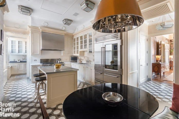 This is a charming kitchen that has an informal dining area next to it. This has a booth-style built-in bench paired with a round black dining table that stands out against the gray and white flooring as well as the off-white cabinetry of the kitchen in the background.