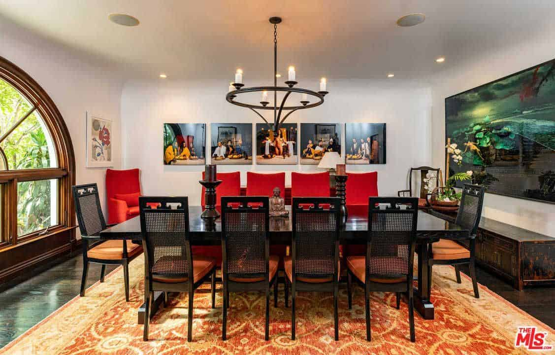 The various colorful wall-mounted artworks stand out against the off-white walls of this dining room. These walls transitions well to a cove ceiling that hangs a simple dark iron chandelier over the dark wooden rectangular dining table contrasted by the red cushions of the chairs.