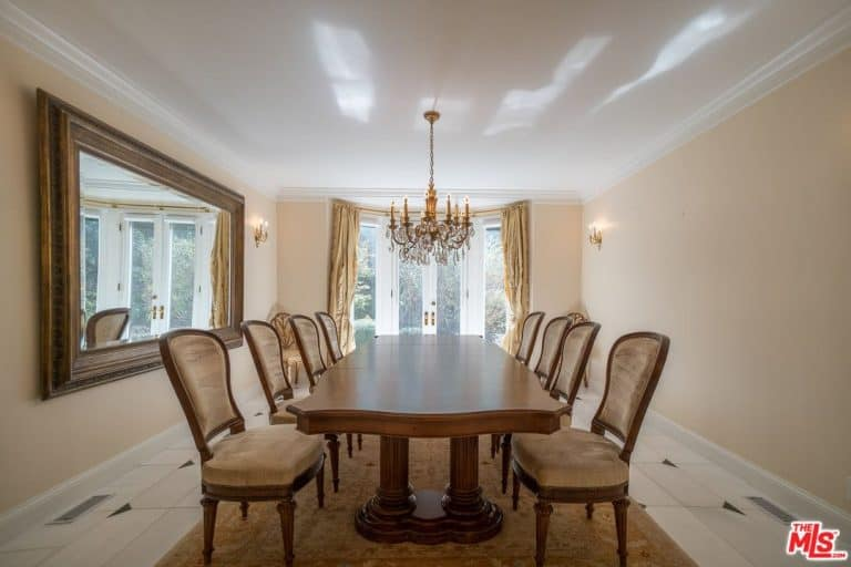 The cheerful light pink walls of this simple formal dining room is paired with a white cove ceiling that hangs a majestic crystal chandelier over the long wooden dining table that is surrounded by beige cushioned chairs that match the beige patterned area rug.