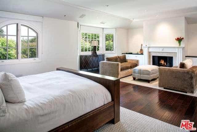 This simple and comfortable primary bedroom has a wooden sleigh bed that has a white bed sheet and pillows matching the bright white walls and cove ceiling. The white mantle of the fireplace fits in to this bright aesthetic contrasted by the brown velvet armchairs of the sitting area.