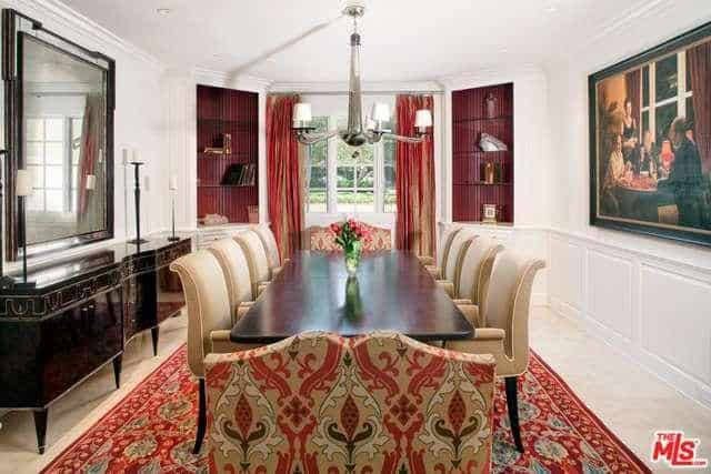 The bright white walls and its bright white wainscoting is adorned with a classical painting and a long waist-high dining room cabinet that matches with the dark wooden dining table surrounded by beige armchairs. This is brightened further by the white cove ceiling and flooring topped with red patterned area rug.