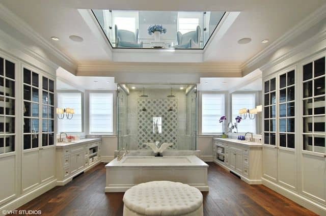 This is a charming primary bathroom with two vanities situated on either side of the room flanking the glass enclosed shower area and the bathtub that is housed in the middle underneath a cove ceiling dominated by a large glass panel with a view of the next floor.