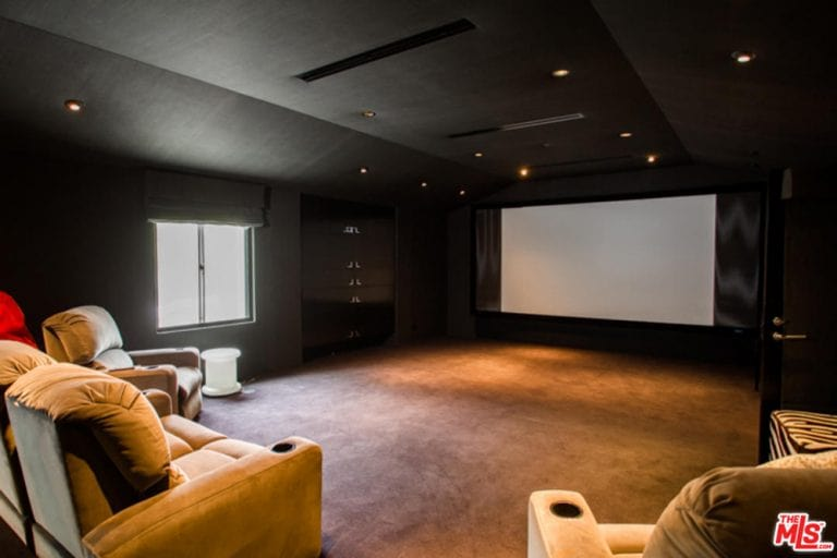 This is an entertainment room with matching black walls and a black cove ceiling to bring the focus on the wide screen at the far end of the room. This is matched with a beige carpeted flooring that blends with the cushioned armchairs.