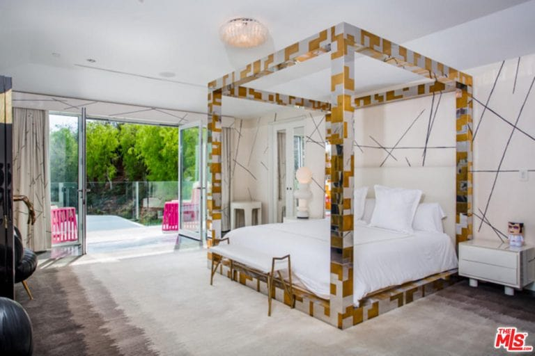 The highlight of this brilliant primary bedroom is the eclectic and modern four-poster bed that looks to be a combination of gold and stainless steel with a futuristic design. This is paired with a white bed that matches with the white walls and white cove ceiling with a flush-mount light.
