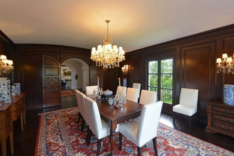 The dark wooden tone that dominates the walls and the hardwood flooring is contrasted by the white cove ceiling that hangs a yellow brilliant chandelier matching with the wall-mounted lamps on the walls. These are complemented by the colorful patterned area rug underneath the dining set.