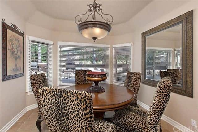 This charming and luxurious informal dining area has animal print on its cushioned dining chairs that surround the circular wooden dining table that is adorned with a brown vase and a large dome pendant light. This room is also adorned by the wall mounted painting and the mirror opposite it.