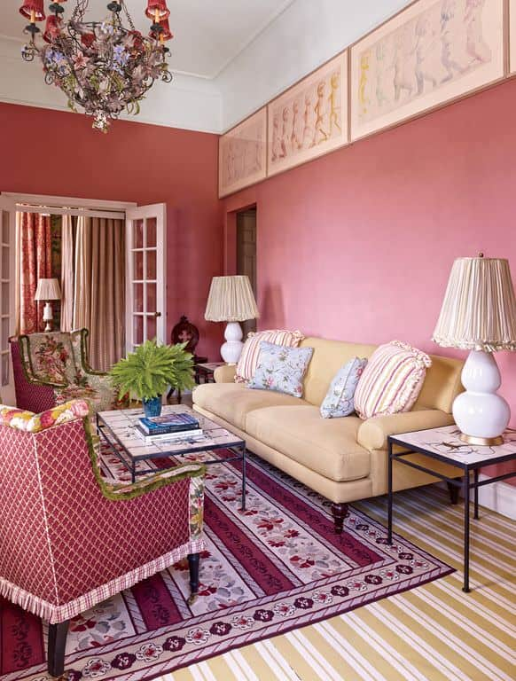 The earthy pink walls of this living room matches the tone of the patterned area rug underneath the beige sofa and the floral cushioned armchair facing the simple coffee table with a wrought iron frame and adorned with a small plant.