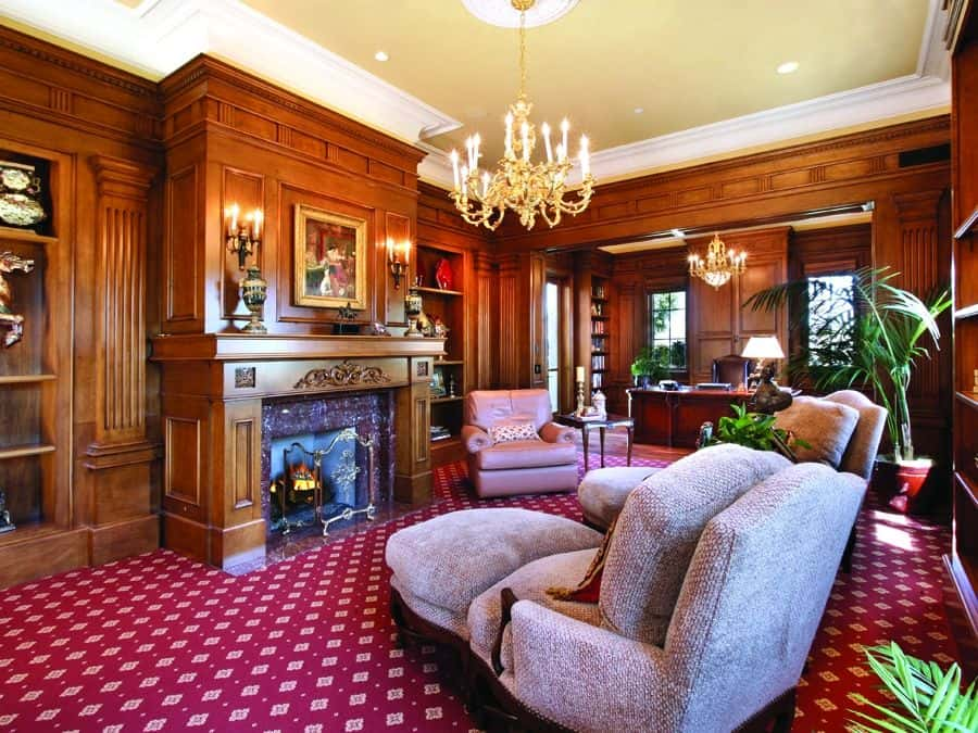 The vibrant red patterned carpeting of the floor gives this office and living room a dynamic of complex aesthetic that gives complement to the elegant finish of the wooden fireplace mantle as well as the book shelves and the beige cove ceiling that has a chandelier.