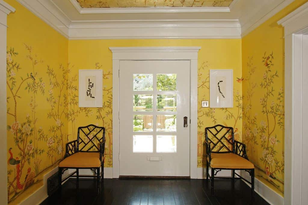 This is a simple and welcoming foyer that is elevated by the beautiful prints and murals on the bright mustard yellow wallpaper. This is contrasted by the dark hardwood flooring and augmented by the white door that blends with the white molding and cove ceiling.