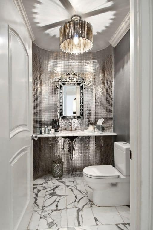 This is a brilliant small bathroom that makes up for its small floor space with its flashy small silver tiles that adorn the curved walls. This matches well with the pendant light of the cove ceiling and contrasts with the white toilet and white wooden door.