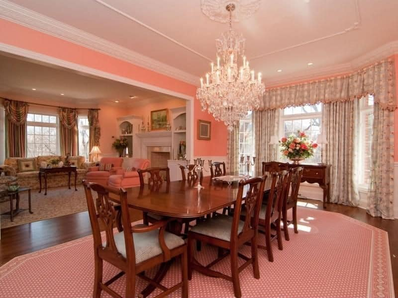 The hardwood flooring of this formal dining room is topped with a patterned pink area rug that contrasts the wooden dining set. This is also contrasted by the white wainscoting and the pink upper walls connecting to the white cove ceiling bearing a white chandelier.