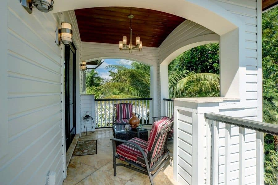 This charming and welcoming front porch has a dark wooden cove ceiling that contrasts the white wooden exterior walls and support columns. These are accented with the modern wall-mounted lamps that pair well with the chandelier hanging over the cushioned iron chairs.