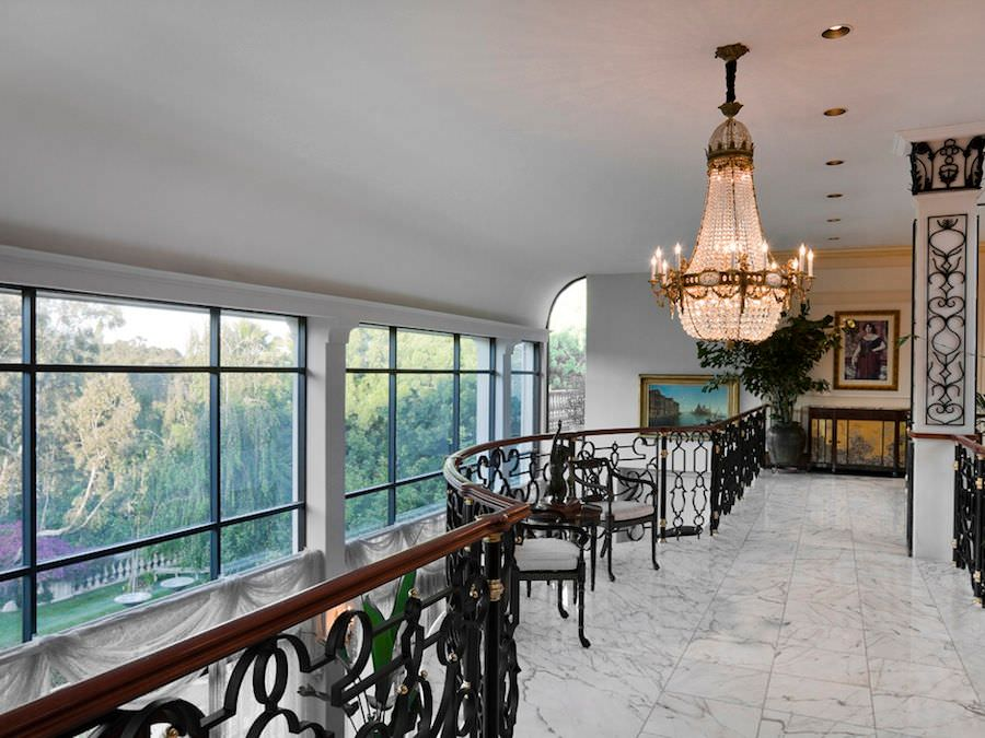 This is the second floor landing of this elegant home that has a tall white cove ceiling curving from the massive glass wall on the side giving a beautiful view for those walking by the wrought iron railings of the landing. This is adorned with a large crystal chandelier in the middle.