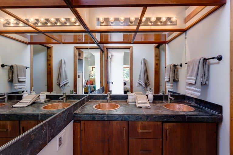 Craftsman style primary bathroom with a stunning ceiling. It offers a double sink with a black marble tiles countertop.