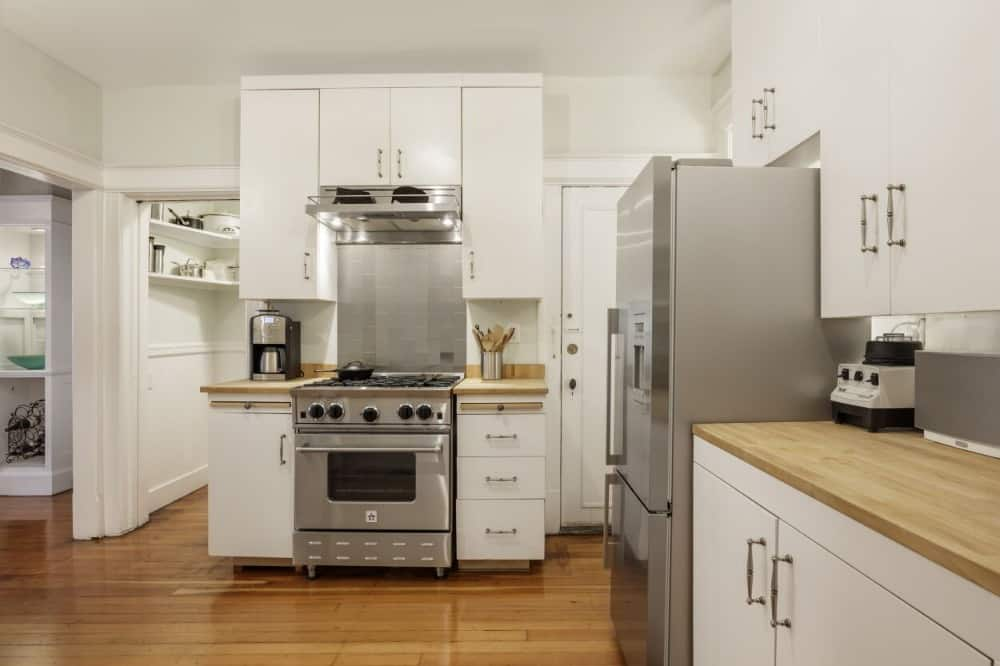 Kitchen with a wooden kitchen countertop and has white cabinetry and kitchen drawers.