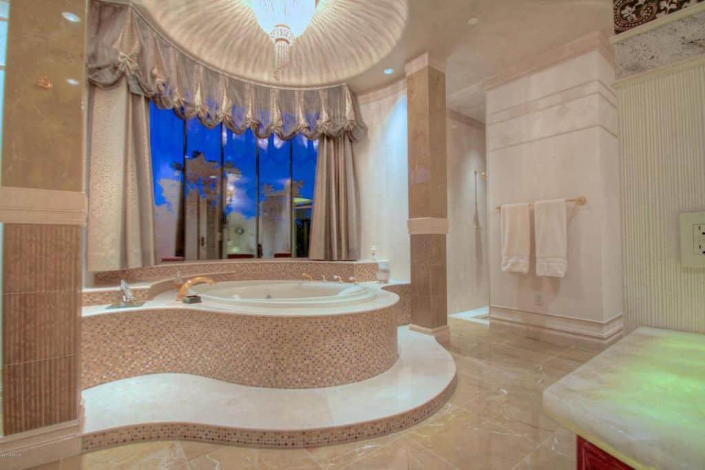 A custom primary bathroom boasting a gorgeous bathtub set under a stunning ceiling lighted by a fancy chandelier. The bathroom also offers a walk-in corner shower room.