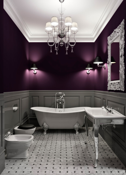 An elegant-looking primary bathroom with purple walls, tiles flooring and a white ceiling. It offers a classy sink counter and a freestanding tub, lighted by a glamorous chandelier.