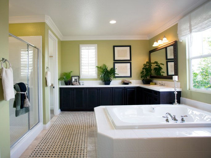 A spacious primary bathroom boasting a large soaking tub and an L-shaped sink counter. There's a toilet room and a walk-in shower room as well.