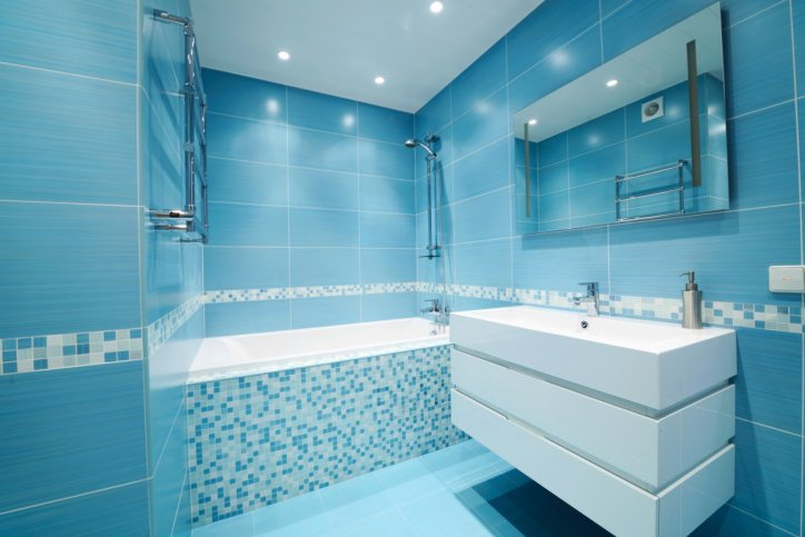 Small primary bathroom boasting blue tiles walls and floors. It offers a single floating vanity sink and a bathtub and shower combo on the side.
