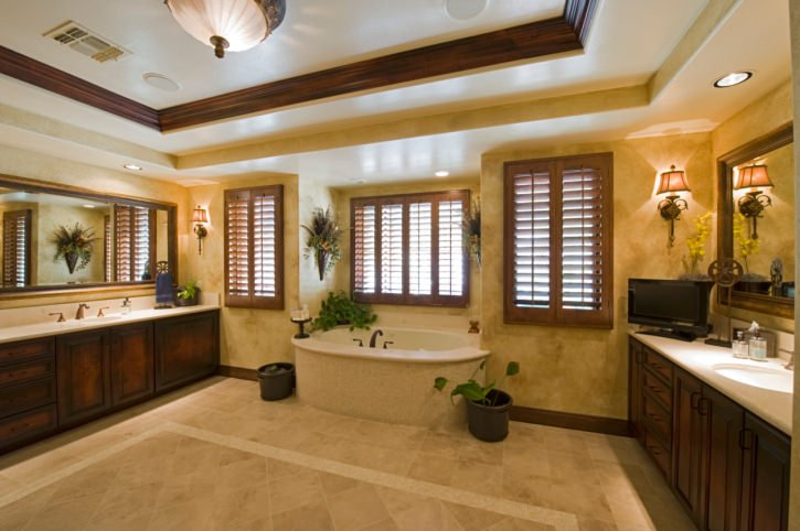 A spacious primary bathroom with a stunning tray ceiling and brown walls, along with beige tiles flooring. There are two sink counters and a freestanding tub.