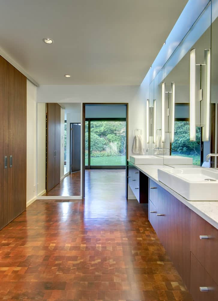A beautiful custom primary bathroom with stylish flooring and a long floating vanity sink counter with a pair of vessel sinks.