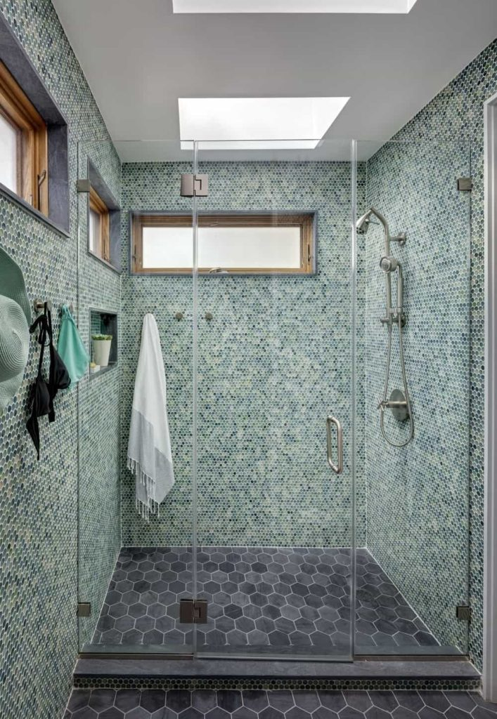 A focused look at this primary bathroom's walk-in shower room surrounded by green tiles walls and black tiles floors, along with a white ceiling with two skylights.