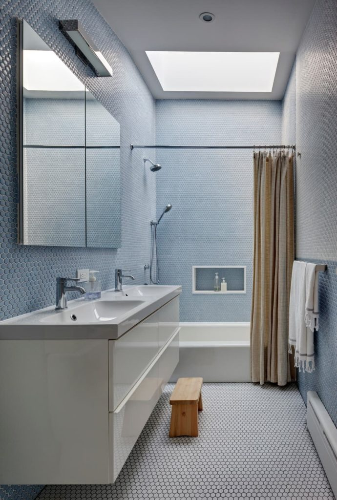 A narrow primary bathroom with blue tiles walls and a ceiling featuring a skylight. It has a double sink and a shower and bathtub combo. The ceiling also features a skylight.