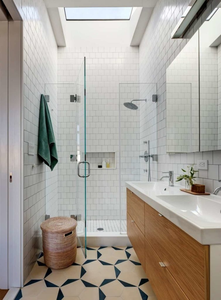 Small primary bathroom with a tall ceiling and tiles walls, along with stylish flooring. It also offers a sink counter with a double sink, along with a walk-in shower set under the room's skylight.