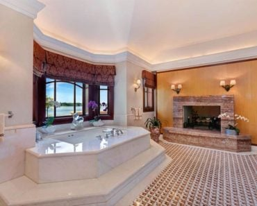 Spacious custom master bathroom with stylish tile flooring, a fireplace, and a drop-in tub on a platform by the windows.