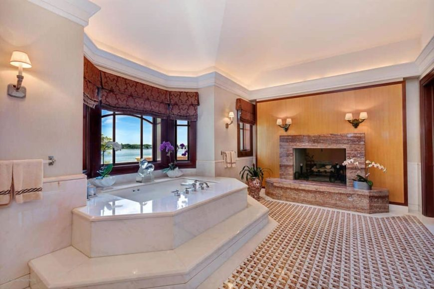 A primary bathroom with custom tiles flooring that looks stylish, along with a large fireplace and a classy drop-in soaking tub on a tiles platform.