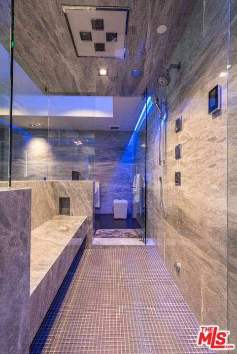 A look inside the large walk-in shower of this custom primary bathroom featuring a stylish wall and ceiling, along with a bench seating.