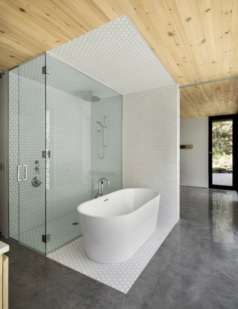 A focused look at this custom primary bathroom's walk-in shower and freestanding deep soaking tub surrounded by white tiles floors, walls and ceiling. The area features gray flooring and a wooden ceiling.