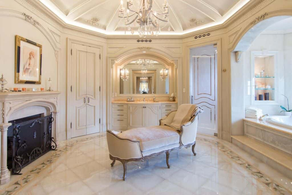 Spacious primary bathroom boasting classy tiles flooring and a stunning ceiling design. The room offers a sitting area set in the middle, along with a gorgeous drop-in tub on the side and a fireplace. The area is lighted by a charming chandelier.