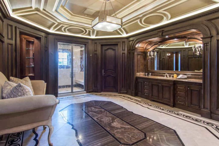 Primary bathroom boasting an elegantly designed ceiling and decorated flooring. It offers a walk-in shower and a classy couch on the side, set in front of the sink counter.