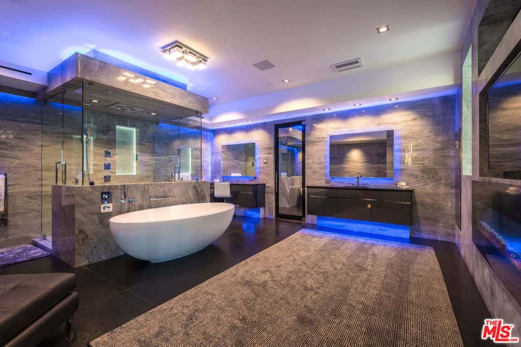 A custom primary bathroom boasting black tiles flooring topped by a brown area rug. The blue lighting engulfing the room looks absolutely striking. The room offers two floating vanities and a walk-in shower room together with a freestanding tub.