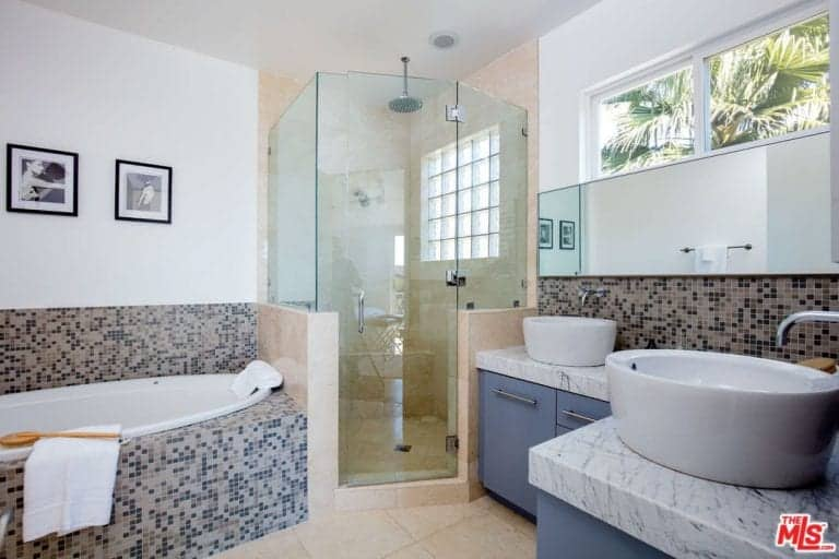 Primary bathroom offering a drop-in deep soaking tub, a corner shower area and a sink counter with a thick marble countertop and has a couple of vessel sinks.