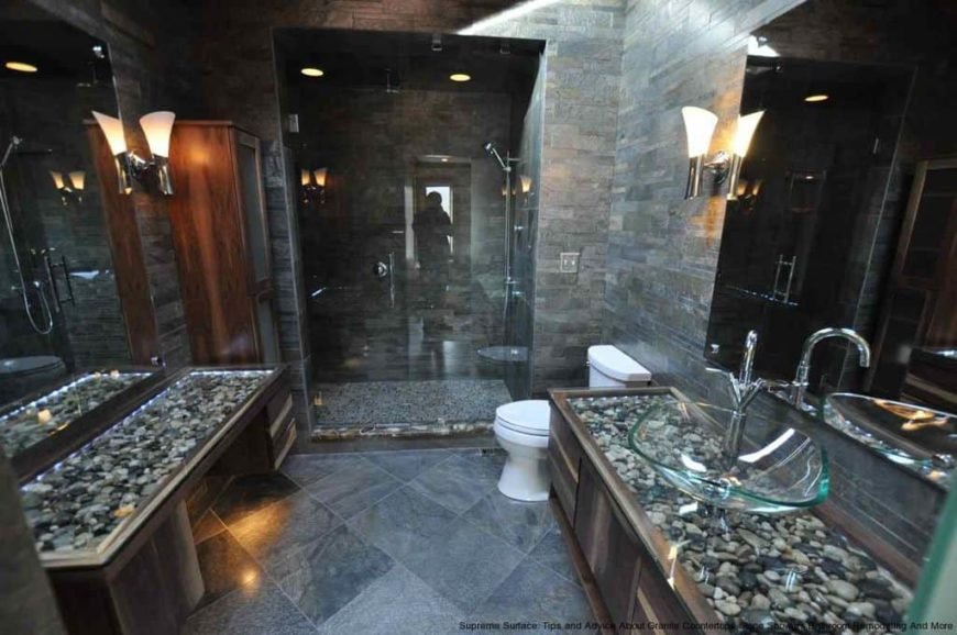 A modern primary bathroom with tiles flooring and walls, along with a walk-in shower room. There's a powder desk and a sink counter, both featuring stylish countertops.