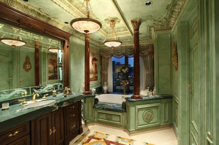 A primary bathroom with a gorgeous decorated custom ceiling matching the green walls. It offers a sink counter with a green countertop and a drop-in soaking tub by the window.