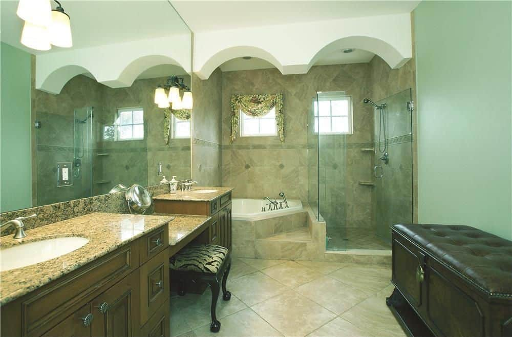 Primary bathroom with green walls, beige tiles floors and a white ceiling. It offers a powder desk in between the two sink counters lighted by wall lights. There's a corner soaking tub and a walk-in shower as well.